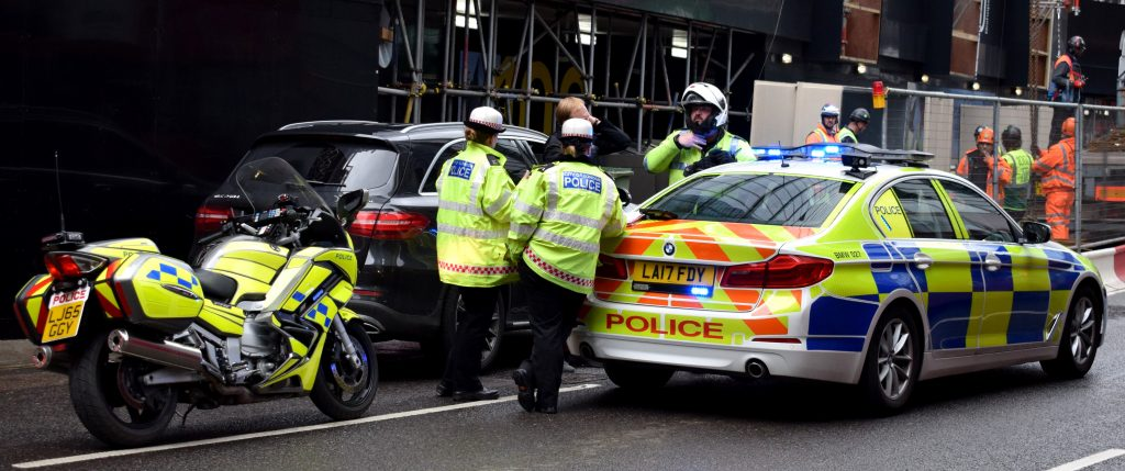 Image of police stood by Police cars